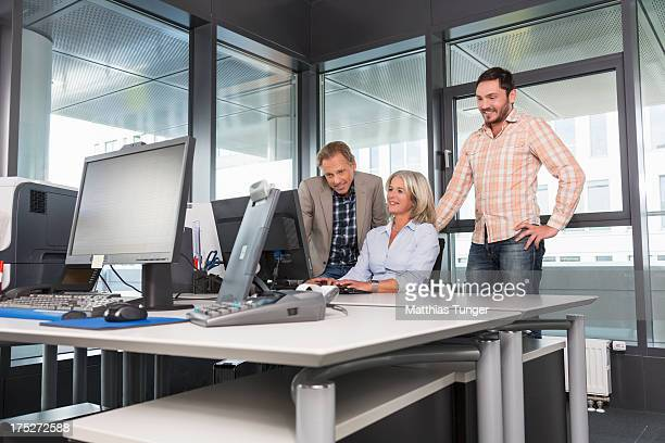 ther people in front of computer monitor