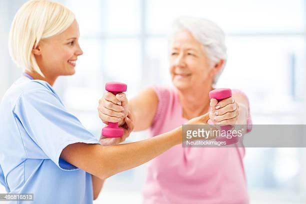 Terapista aiutando donna anziana sollevamento manubri