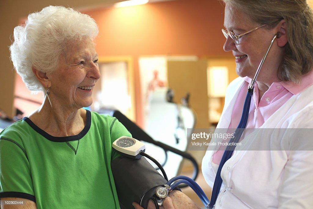 Therapist checking blood pressure of senior female : Stock Photo
