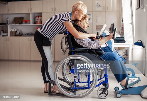 Senior Woman On Wheelchair Having Daily Exercise On Exercise Bike