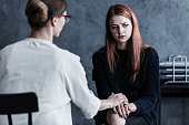 Dedicated therapist looking after her patient by holding her hand in grey office