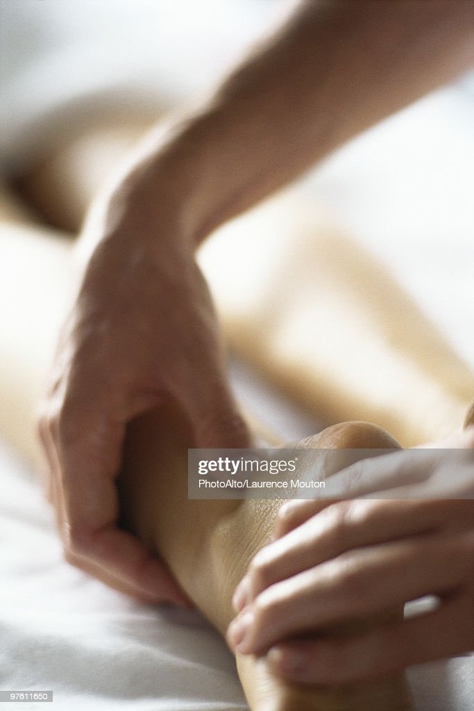 Therapist performing acupressure on patient's ankle, close-up