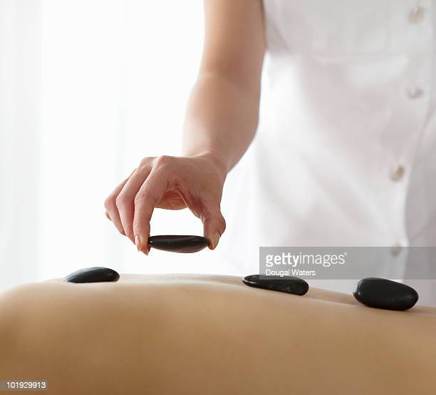 Therapist placing hot stones on womans back.