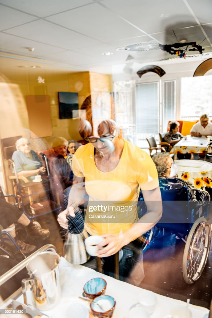 Therapist Serving Coffee To The Seniors At The Retirement Center : Stock Photo