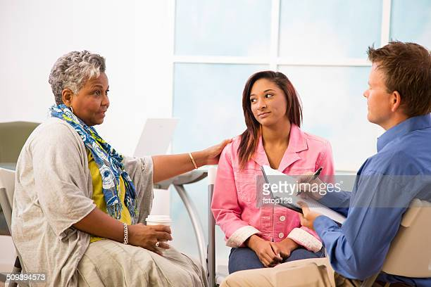 Therapist takes notes in counseling session. Mother, daughter clients.