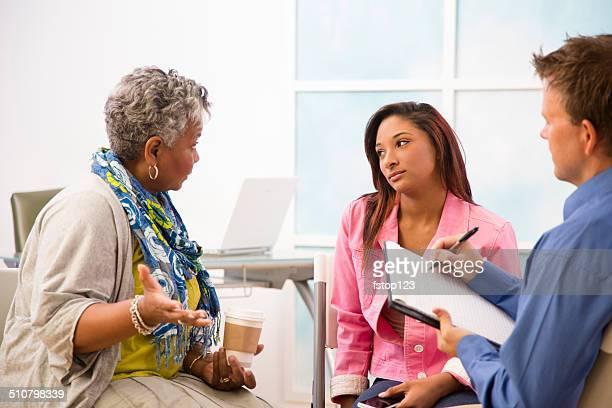 Therapist toma notas da sessão de aconselhamento. Mãe, filha clientes.