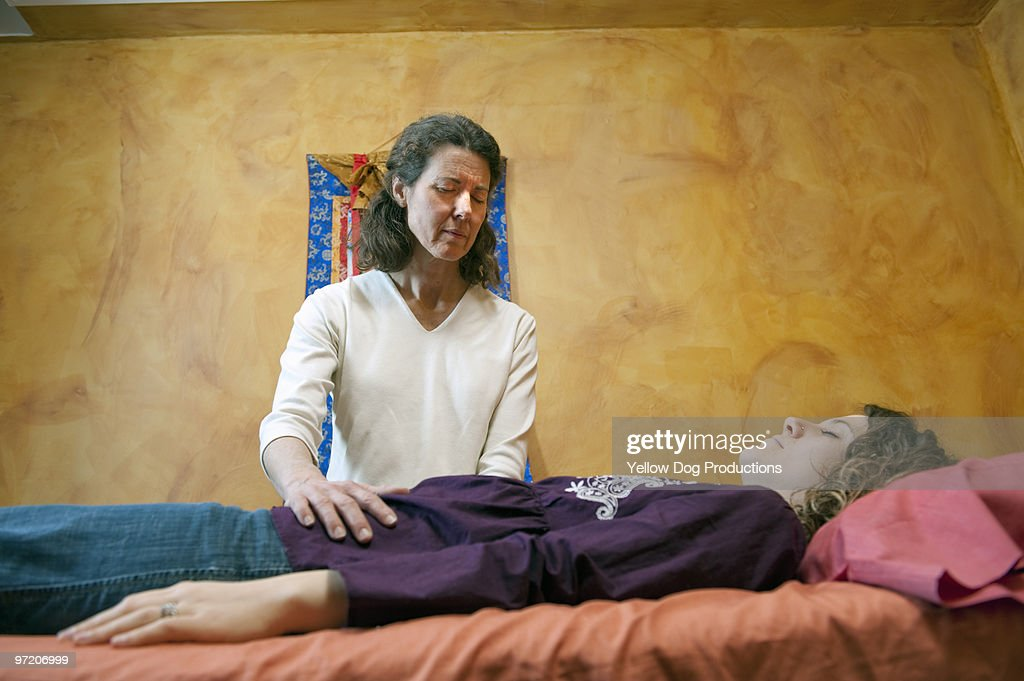 Therapist treating client on massage table