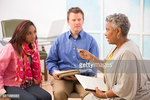 Therapist with man, woman clients during couple counseling session.