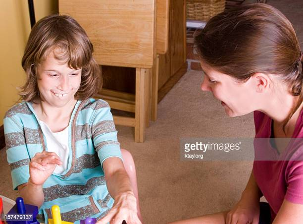 Therapist working with cute autistic girl