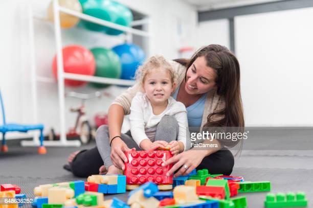 Therapeuten arbeiten mit drei Jahre alten Mädchen und spielen mit Baustein Spielzeug