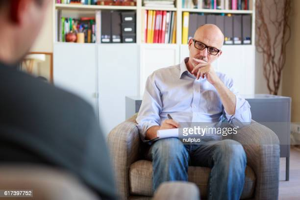 Therapy session, adult man talking to his psychotherapist