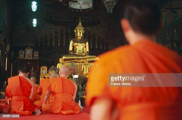Theravada buddhist monks meditating in a temple