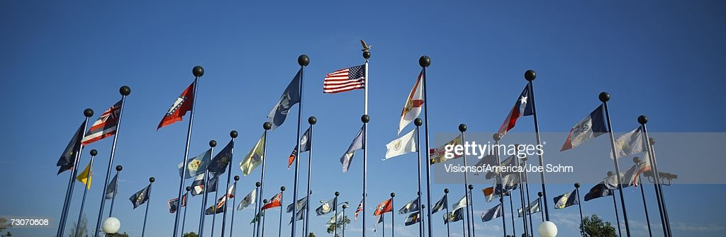 'There are 50 State Flags waving in the wind on flagpoles equal distant apart against a blue sky, with the American flag in the center. These are located at Sea World.' : Stock Photo