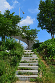 There is a marble staircase with grass growing up, overpasses and street lamps.