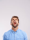 Studio shot of a handsome young man screaming in anger against a gray background