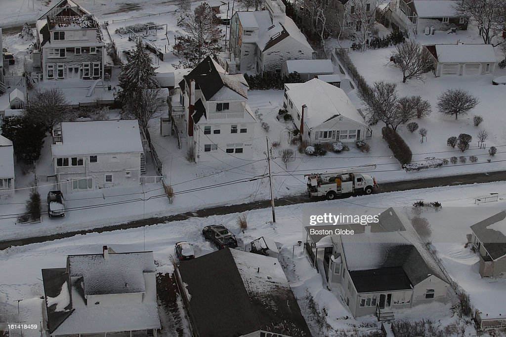 There's still no power in Humarock, Mass., as a vehicle makes its way through a flooded street with mounds of sand on both sides of the roadway after a blizzard hit New England.