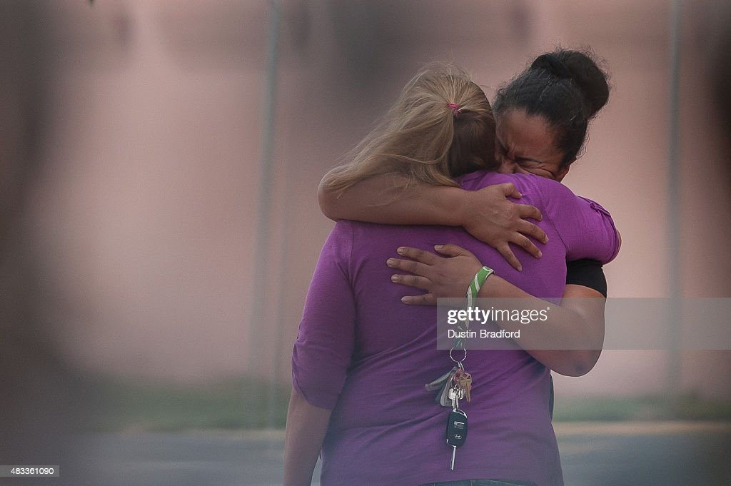 Theresa Hoover the mother of the Aurora Colorado theater shooting victim Alexander 'AJ' Boik is comforted outside of the Arapahoe County Justice...