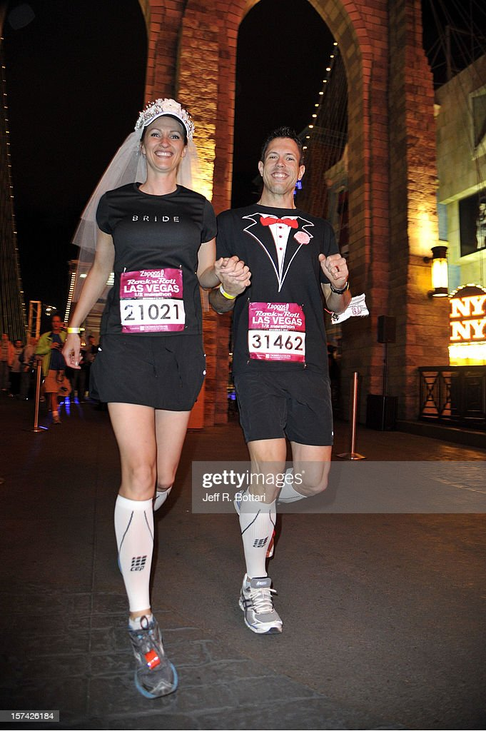 Theresa Johner (L) and Eric Jensen of Utah rejoin race participants after getting married at the New York-New York Hotel & Casino's Brooklyn Bridge replica during the Zappos.com Rock 'n' Roll Las Vegas Marathon and Half-Marathon on December 2, 2012 in Las Vegas, Nevada.