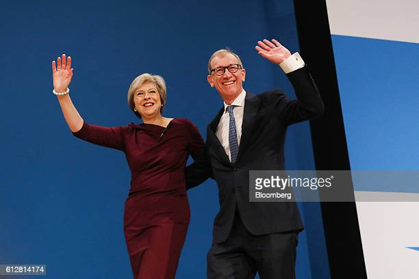Theresa May UK prime minister and leader of the Conservative party and her husband Philip May wave to the crowd after she delivered the closing...