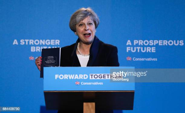 Theresa May UK prime minister and leader of the Conservative Party holds up a copy of her party's general election manifesto titled 'Forward...