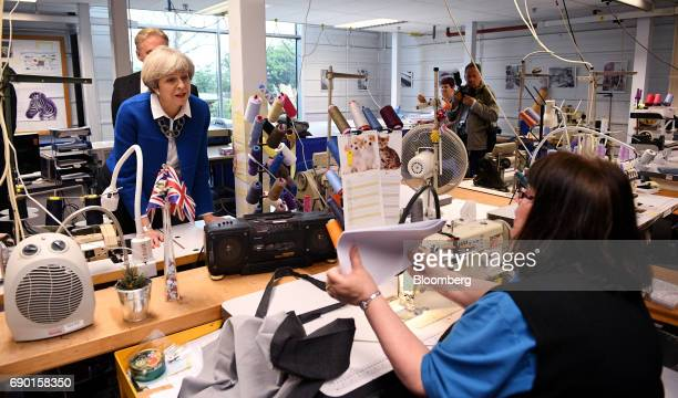Theresa May UK prime minister and leader of the Conservative Party speaks with a worker while touring a uniform factory during a general election...