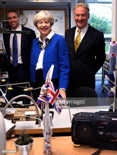 Theresa May UK prime minister and leader of the Conservative Party center tours a uniform factory during a general election campaign event in...