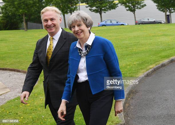 Theresa May UK prime minister and leader of the Conservative Party right arrives at a uniform factory during a general election campaign event in...