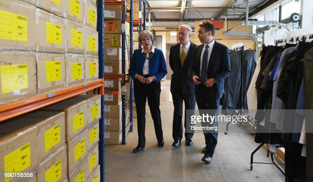 Theresa May UK prime minister and leader of the Conservative Party left tours a uniform factory during a general election campaign event in...