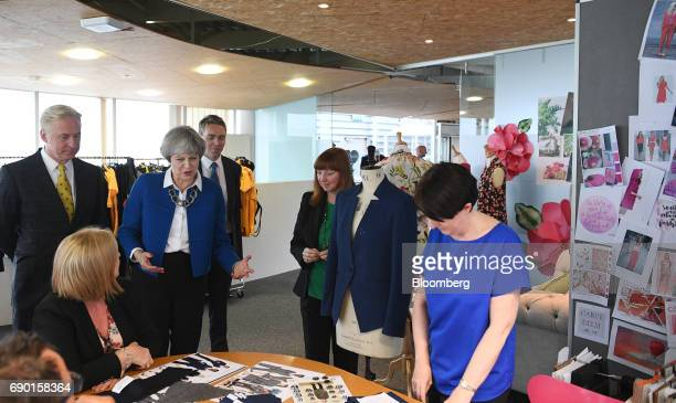 Theresa May UK prime minister and leader of the Conservative Party third left speaks with workers while touring a uniform factory during a general...