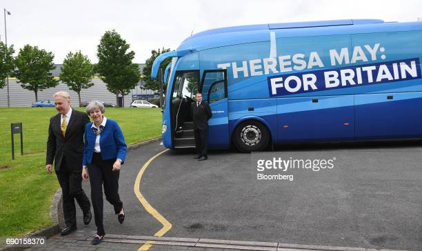 Theresa May UK prime minister and leader of the Conservative Party center exits a tour bus during a general election campaign event in Accrington...