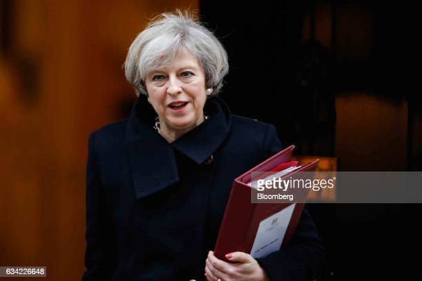 Theresa May UK prime minister carries a document folder as she leaves 10 Downing Street to attend the weekly questionandanswer session in parliament...