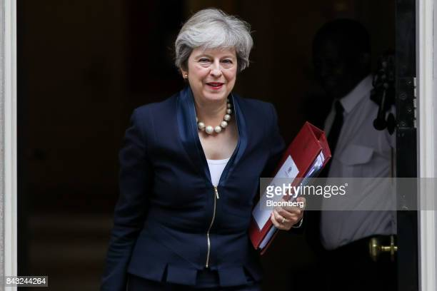 Theresa May UK prime minister carries a document folder as she leaves number 10 Downing Street on her way to attend the weekly questions and answers...