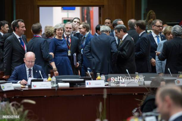 Theresa May UK prime minister center left stands beside Tim Barrow UK permanent representative to the European Union ahead of roundtable talks with...