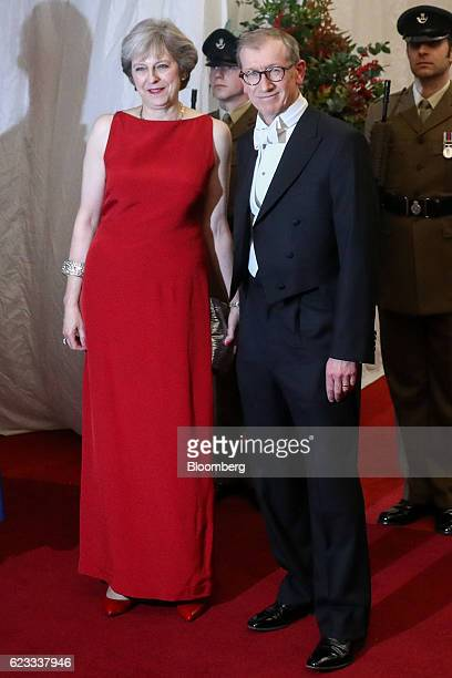 Theresa May UK prime minister left and her husband Philip May pose for photographs as they arrive at the annual Lord Mayor's Banquet at the Guildhall...