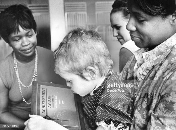 Theresa Skelton Studies the Plaque Awarded to Buttercup Hall of Unit 'D' Mrs Frances Nalley holds Theresa as left Mrs Evelyn Riley in charge of hall...