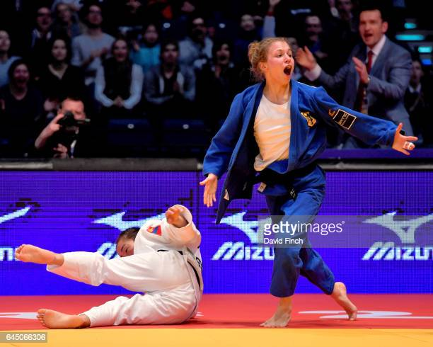 Theresa Stoll of Germany triumphantly rises after throwing Sumiya Dorjsuren of Mongolia for a wazari in extra time to win the u57kg final and gold...