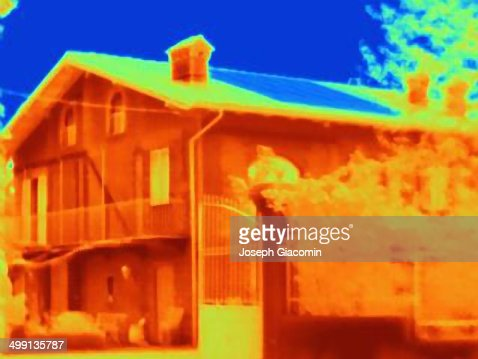 Thermal image of a house with solar cells on the roof. Absorbing the light energy, the solar panel appears cold in the image