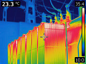Thermal image of electrical transformer. Colors represent various temperatures, defined with rainbow Celsius scale on right side of image. Temperature on upper left corner is a temperature of a point