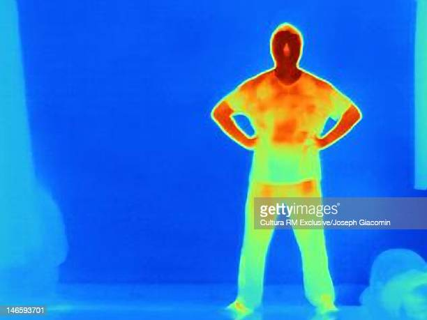 Thermal image of man standing against wall