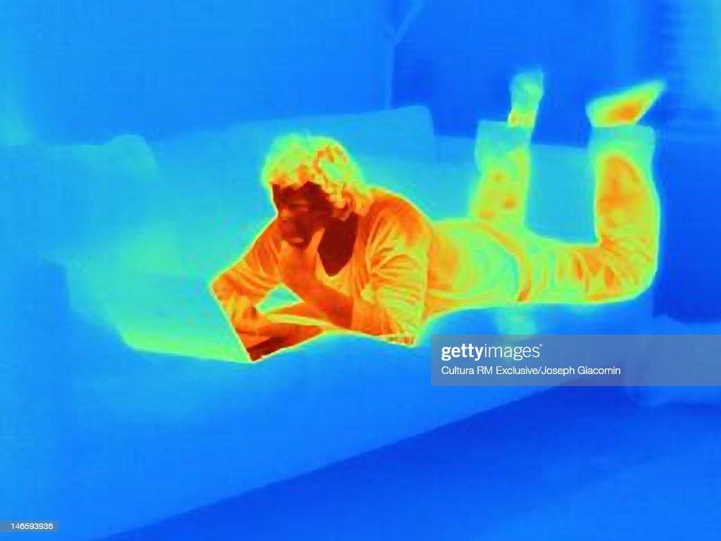 Thermal image of man using laptop on sofa : Stock Photo
