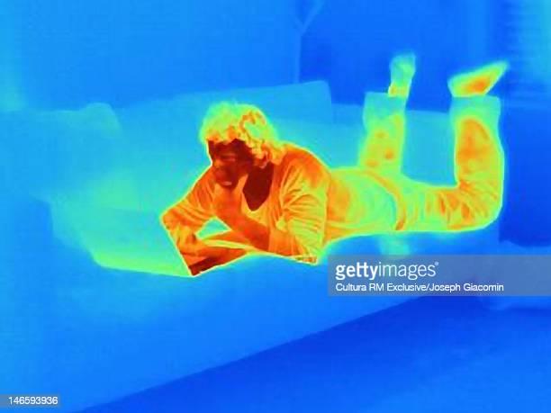 Thermal image of man using laptop on sofa