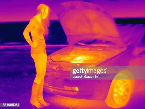 Thermal image of woman looking at automobile engine on roadside