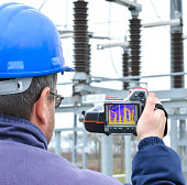 Engineer works with thermal infrared camera. Electrician is in thermographic inspection in power substation, he checks temperature and heating of transformer in power substation.