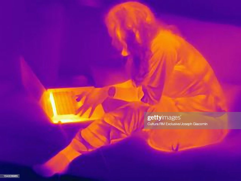 Thermal view of man using laptop : Stock Photo
