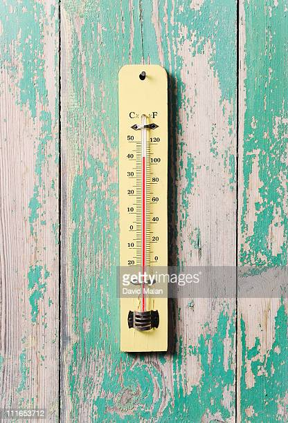 Thermometer on a weathered wooden wall