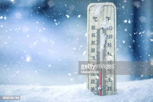 Thermometer on snow shows low temperatures - zero. Low temperatures in degrees Celsius and fahrenheit. Cold winter weather - zero celsius thirty two farenheit : Stock Photo