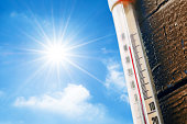 Thermometer with a high temperature reading on a scale, against a background of bright sun and a blue sky with clouds. The concept of hot, dangerous weather, global warming