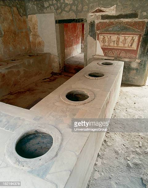 Thermopolium of Asellina tavern specializing in the sale of hot beverages Stone bar with holes to place the amphorae containing drinks At the bottom...
