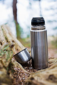 Thermos on forest wood, close-up