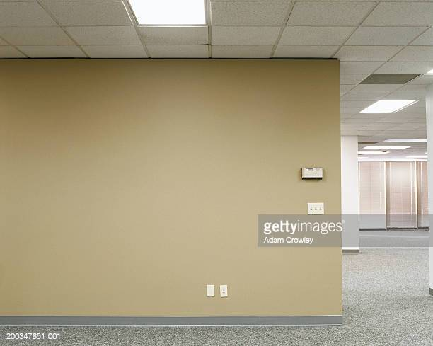Thermostat, outlets and light switches on wall in empty office